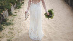 Mariée avec chaussures à la main marchant sur le sable
