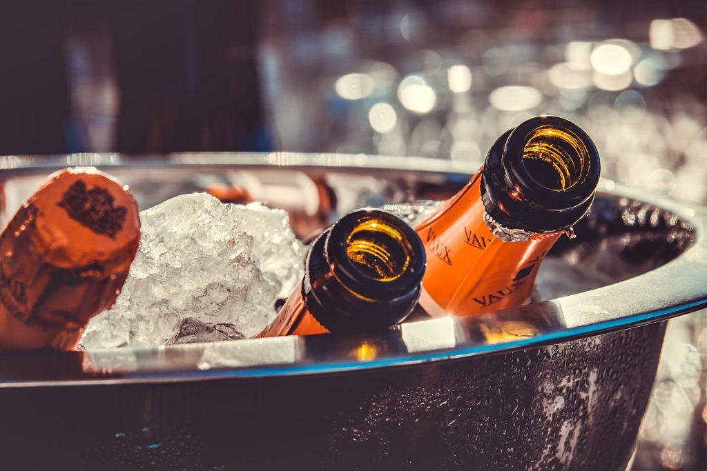 seau à champagne rempli de glace avec trois bouteilles