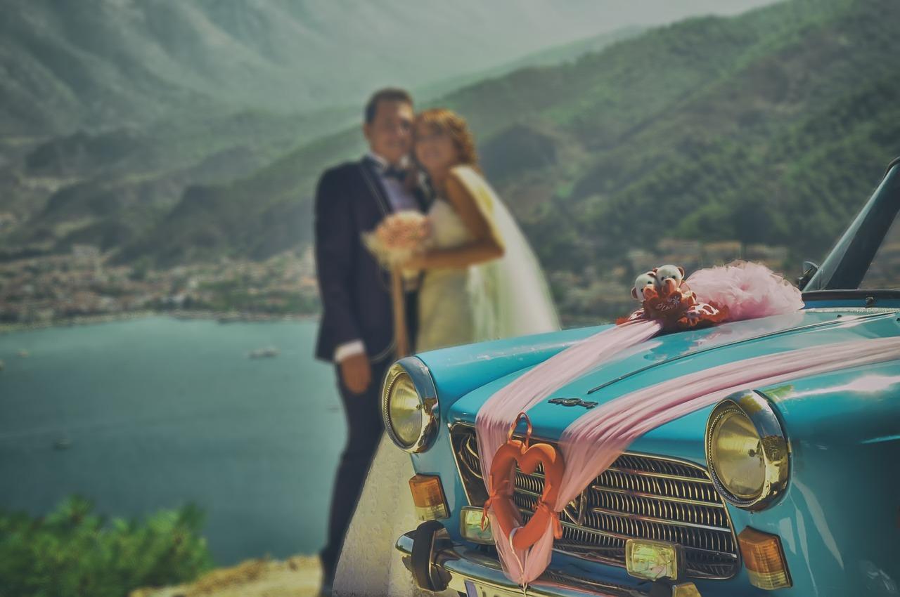 mariés posant pour une photo près d'une voiture bleue décorée avec rubans roses